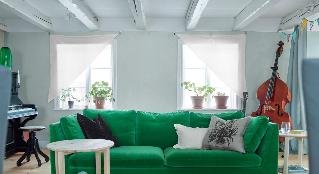 Wohnzimmer mit einem 3er-Sofa in Grün und selbst gebastelten