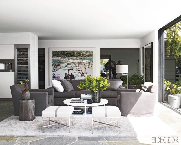 Black and grey living room with lots of natural light. Modern minimalist style furniture enlivened with oversized art and a pretty vignette on the coffee table. Xoxo