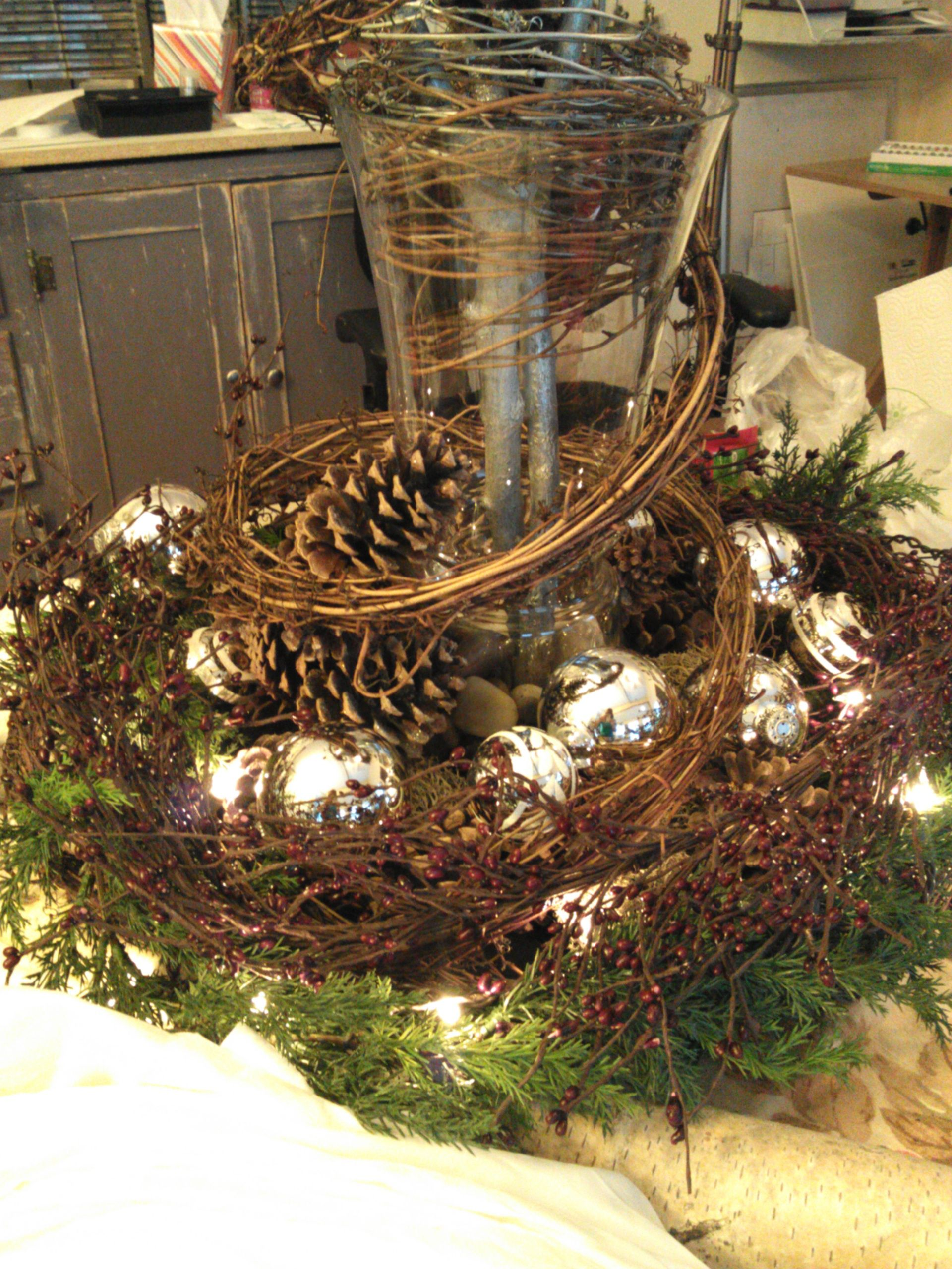 Experimenting with table centerpiece.  Silver glass balls, grapevine, artificial evergreen garland, pinecones.