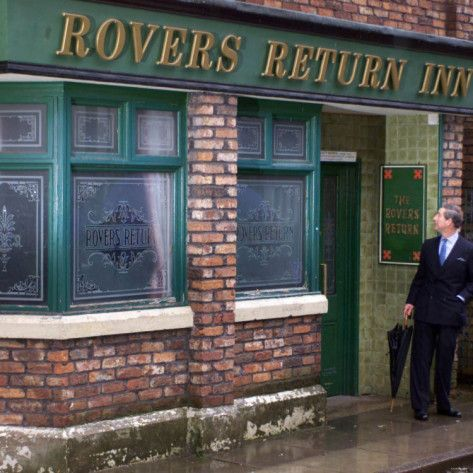 "Prince Charles Shelters from the Rain on the Set of ""The Soap Coronation Street"""