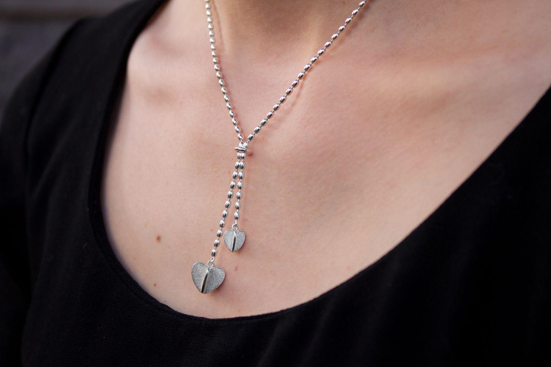 Suloisessa omppusessa yhdistyy kaksi sydäntä. Koruissa vuorottelee matta ja kiiltävä pinta. Ketjuna on kaunis oliiviketju.  Kaulakorun pituus yhtymäkohtaan on 45cm Korun koko mitta on n. 50cm. Koru on 925 hopeaa. Toimitusaika 1-3 arkipäivää.