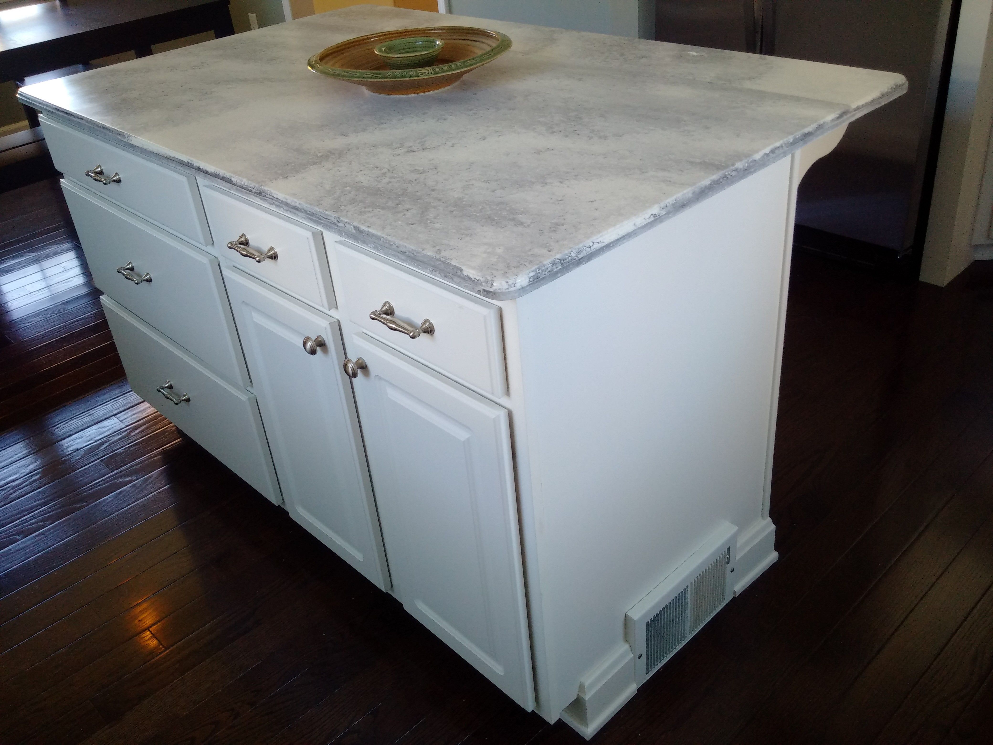 Island cabinets with Solid surface counter and overhang. Note heat ...