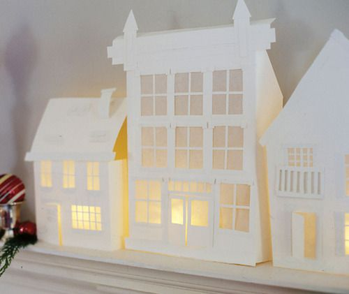 DIY Paper Mantelscape Templates from Country Home here. From Country Home:    A  paper village lights up our holiday mantel. We used card stock and waxed paper to create the village; votive candles inside glass holders illuminate the scene. Embellish village as desired: Church, Storefront, House, House 2.
