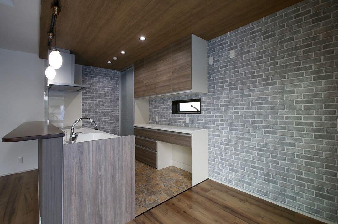 キッチンの背面をレンガ調のクロスにすることで 木目のキッチン