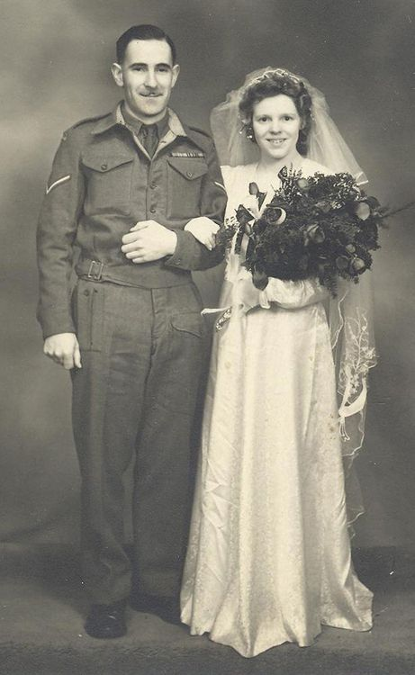 This couple who married in Leeds, England is unidentified, but I love the bride's shy smile and her huge bouquet of roses.
