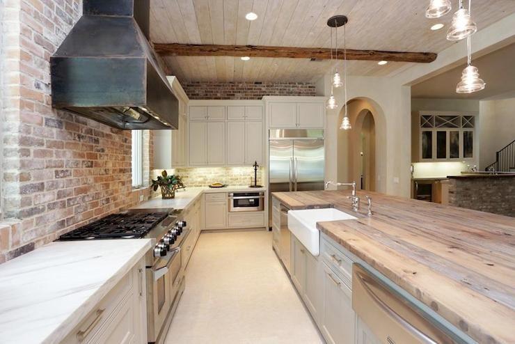 pale gray cabinets; raw steel hood; exposed brick backsplash