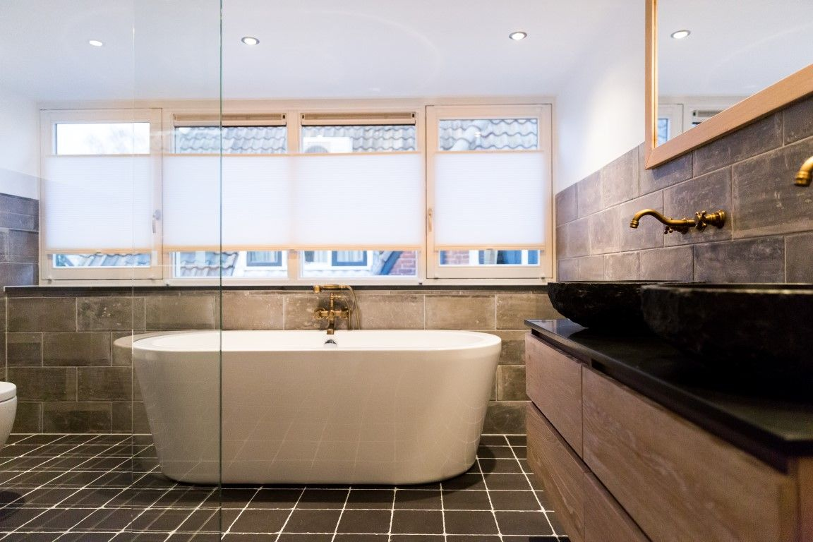 Prachtige sfeervolle badkamer met keramische wand en vloertegels