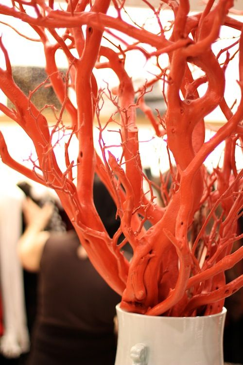 orange spray painted twigs on a giant vase