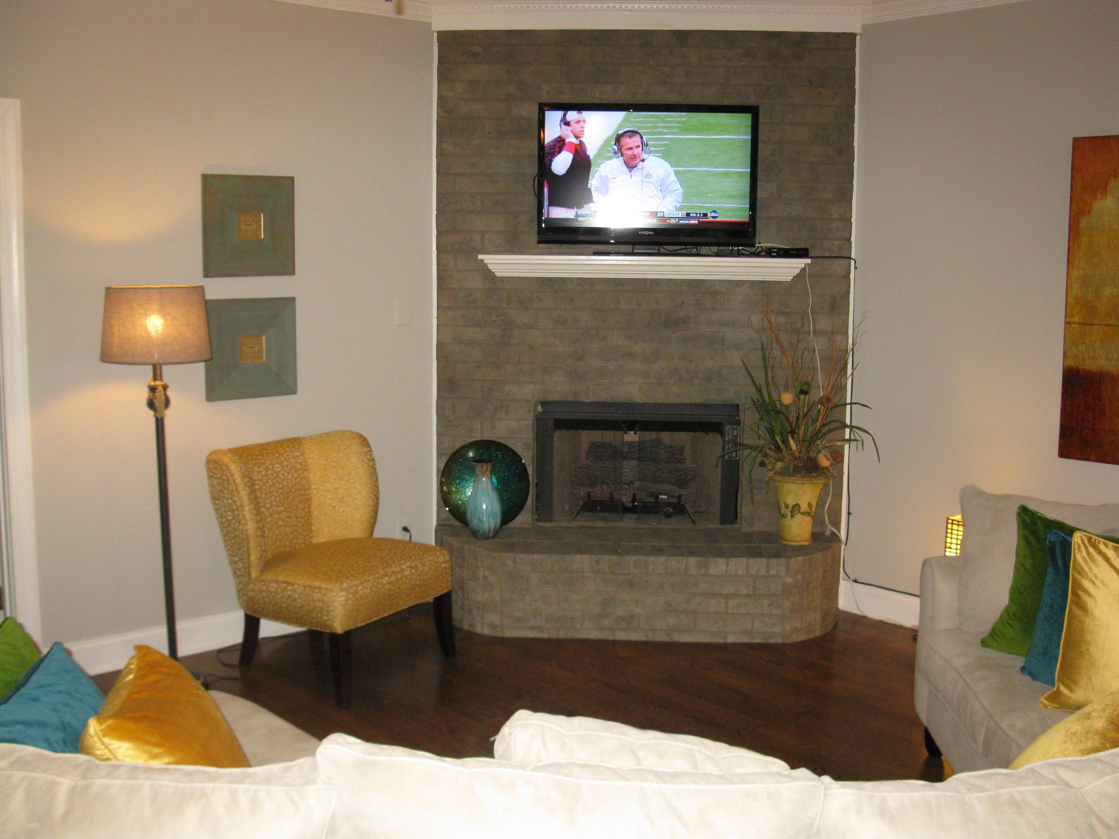 A salmon colored brick fireplace gets a new lease on life with gray