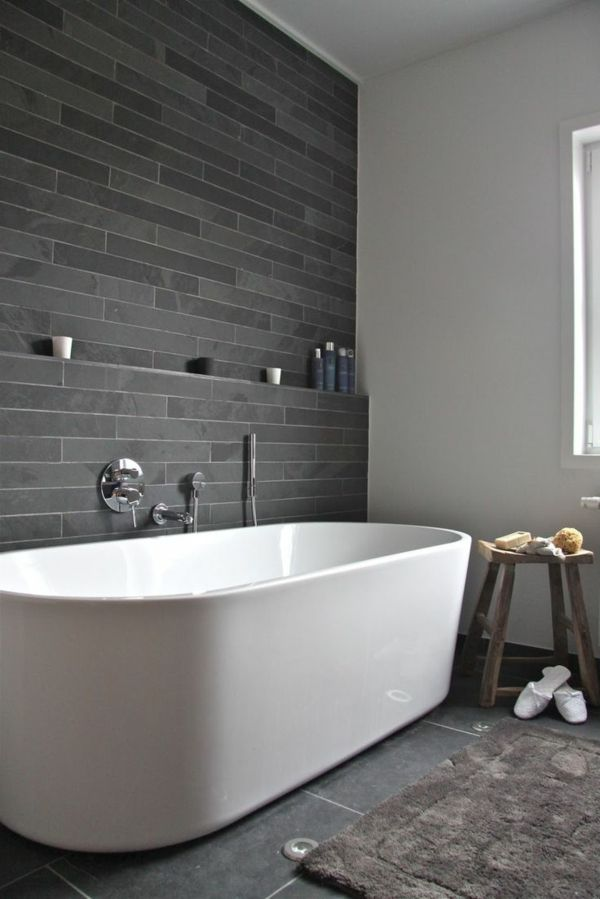 salle de bains grise un mur gris dans la salle de bains et une baignoire blanche