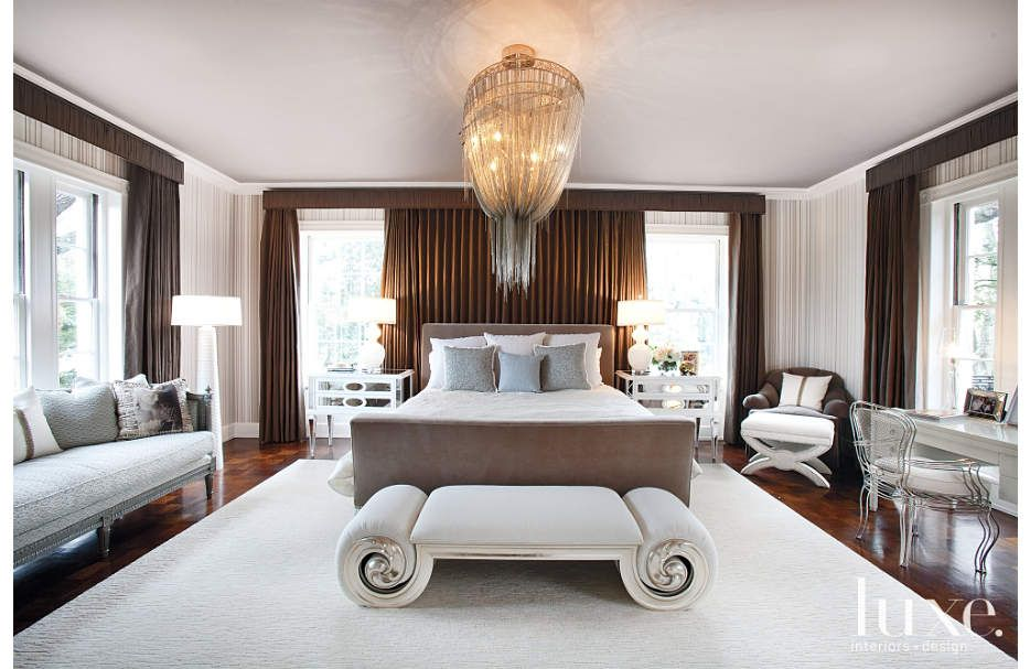 A Barlas Baylar chandelier from Hudson Furniture hangs above an Allan Knight bed and Christopher Guy bench in this master bedroom by Laura Umansky.