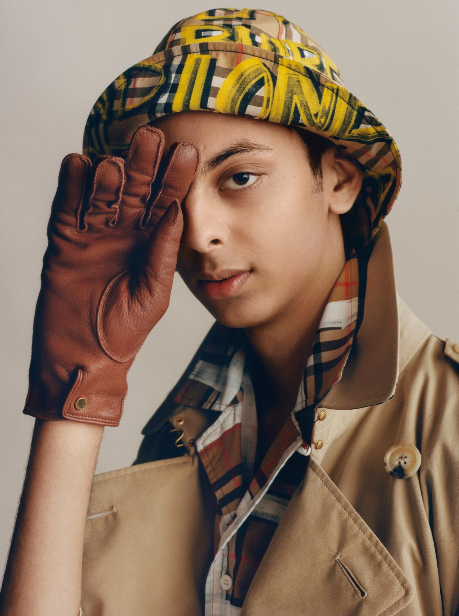5348ac0fa07 Yusuf in a graffiti-print bucket hat and  Burberry Chelsea trench coat.  Styled by Rúben Moreira. Photographed by Thurstan Redding  TrenchReimagined