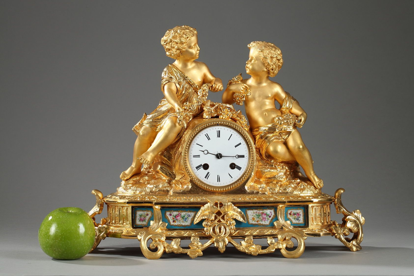 An ormolu mantel clock with two children picking fruits and flowers, sitting on a rock, above an oval  base richly decorated with interlacing, foliated scrolls and polychromatic porcelain pl