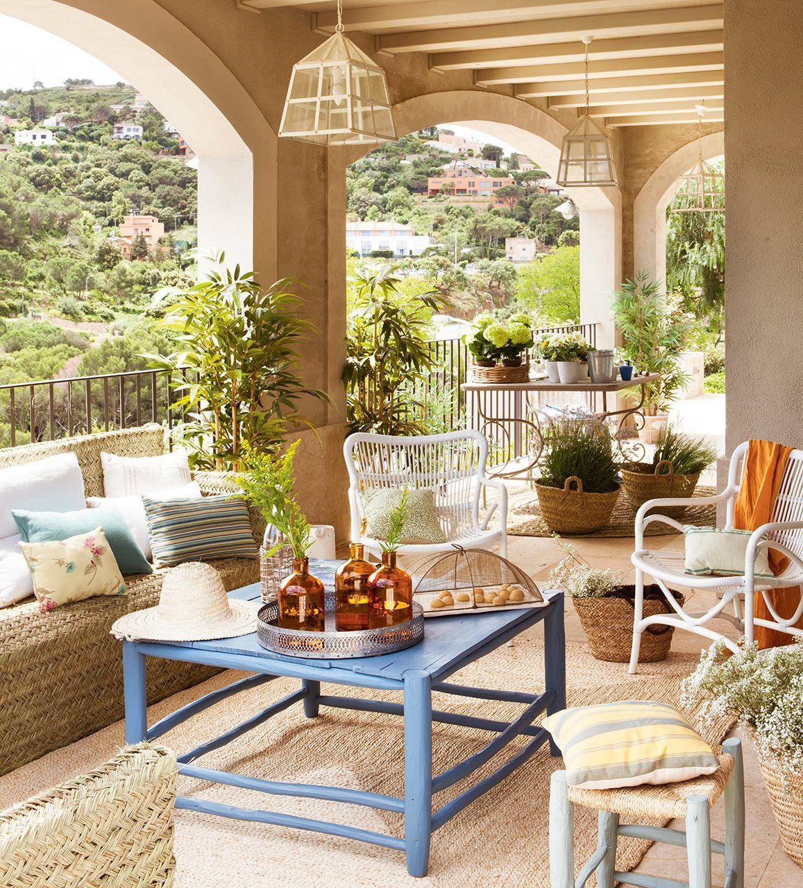 Porche con muebles de mimbre y mesa de centro azul de for Muebles porche