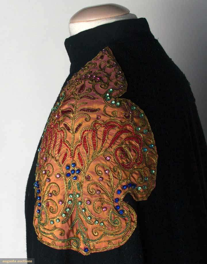 """ELSA SCHIAPARELLI EVENING CAPE, 1937-1938 Black wool, floor length, pale orange cartouche shaped shoulder appliques w/ gold soutache & bead & jewel Lesage embroidery, high band collar, double row of welted button holes at either side of opening, unlabeled except for shop label """"Importer Josephine Smith, Springfield, Mass"""", pale orange lining. Detail"""