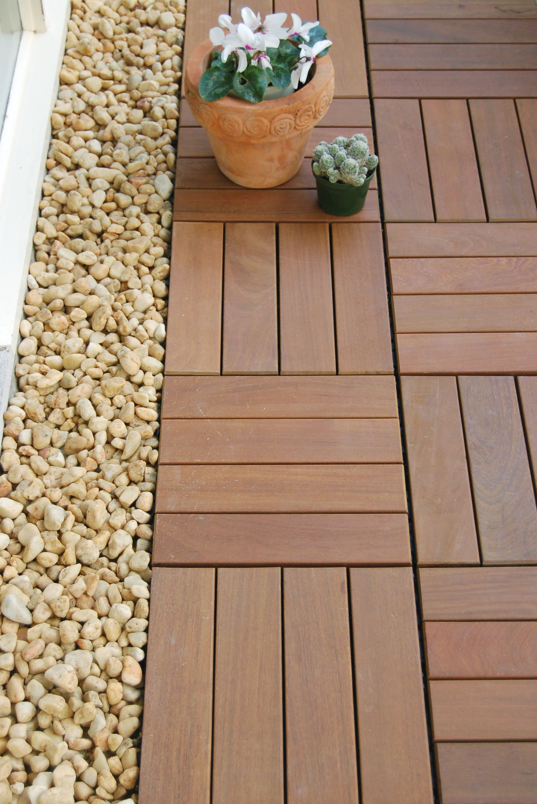 A row of pebbles saves cutting any patio tiles to fit a gap