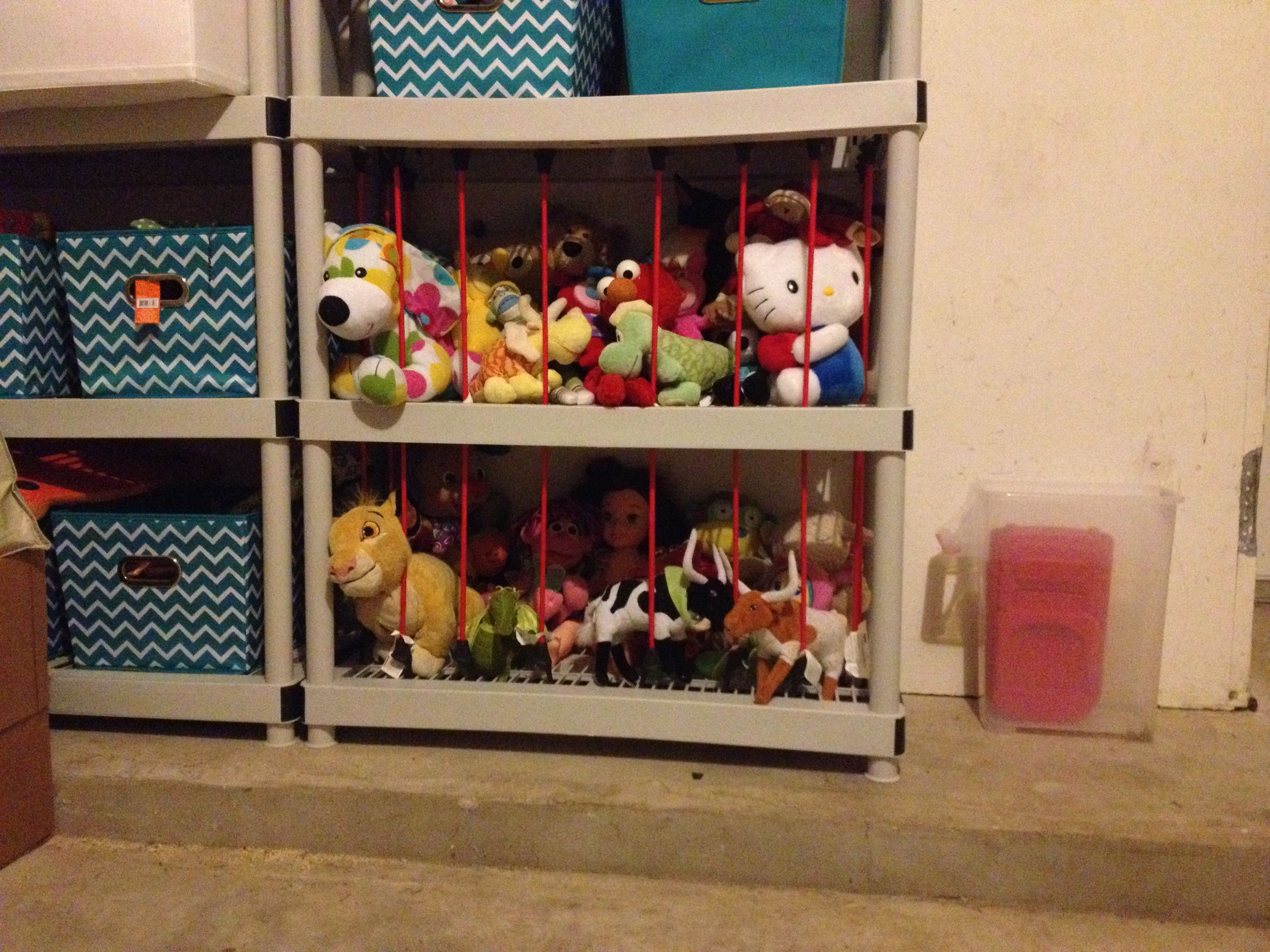 """A SIMPLE STUFFED ANIMAL """"ZOO"""": Wanted an out-of-the-way place to store the girls' stuffed animals but also allow them access. So I just took two of the lower shelves in our garage shelving and added 24"""" bungee cords to fronts and sides. Each cord stretches from bottom shelf through the middle shelf to the top."""