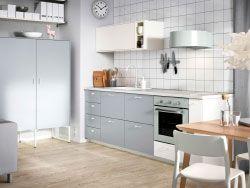Køkken med hvide låger og grå skuffer kombineret med grågrønne hvidevarer.