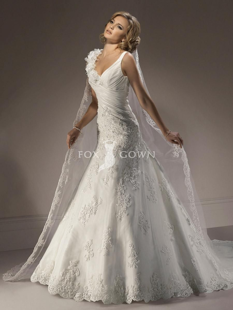 designer lace wedding dress with romantic flowers across shoulder and scallop edged veil