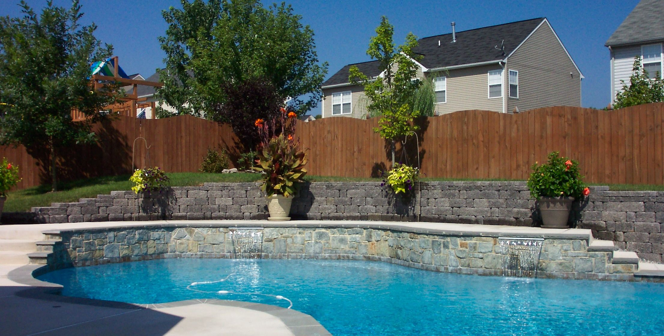 Outdoor fireplace built into retaining wall pool for Pool design retaining wall