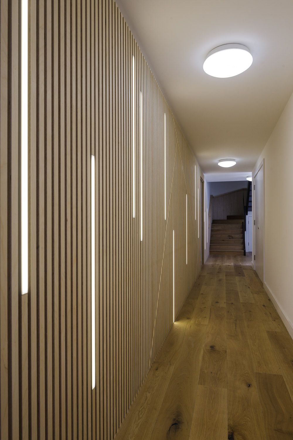 plywood lighting. led lighting dissecting a wall of plywood strips in corridor at wilberforce road this could
