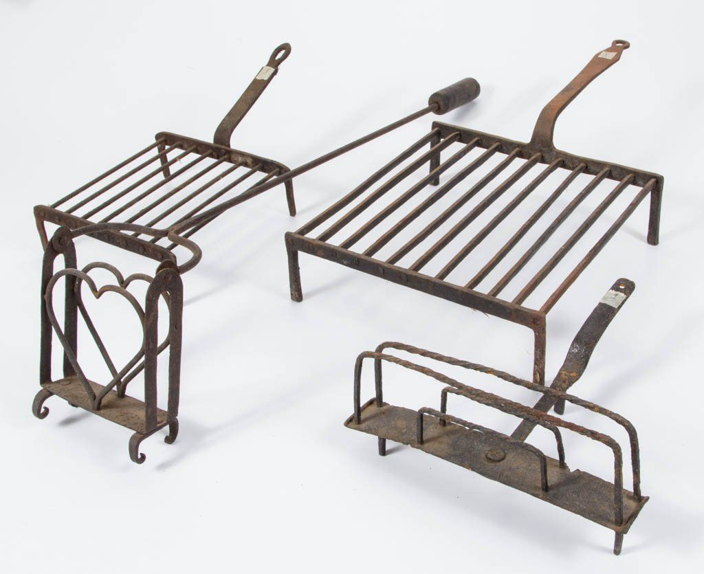 "Assorted wrought iron hearth articles, comprising a heart-form toaster with wooden handle grip, a rotating toaster, and two gridirons. 18th/19th century. 11"" to 33"" L"