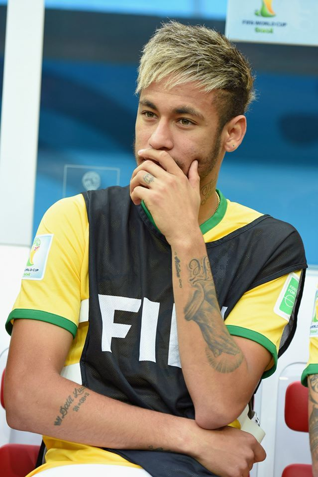 An injured Neymar of Brazil looks on from the bench during ...