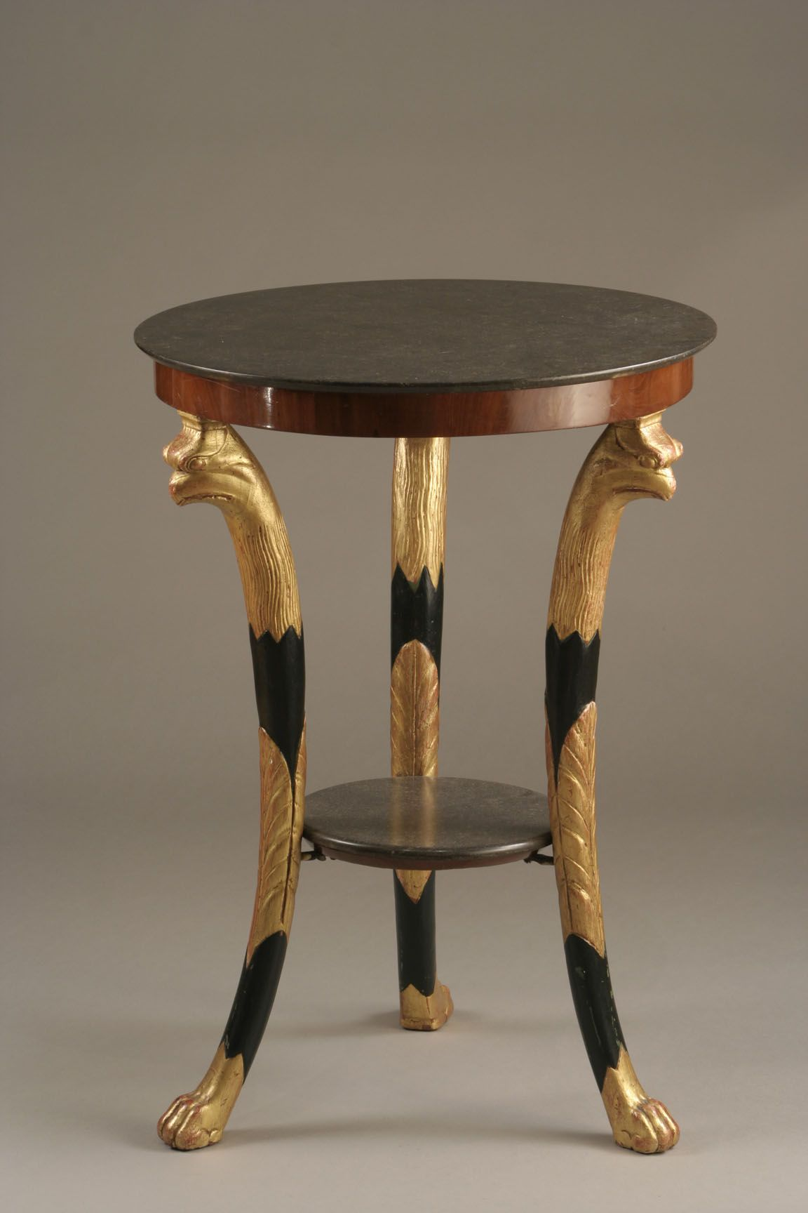A French Empire pedestal table.  A gilt-wood tripartite feet pedestal table. Apron in mahogany with a Brussels gray marble on top. Three blackened-wood and gilt-wood feet, carved as griffins, and linked by a round tray covered by a smaller gray marble. Circa :1800