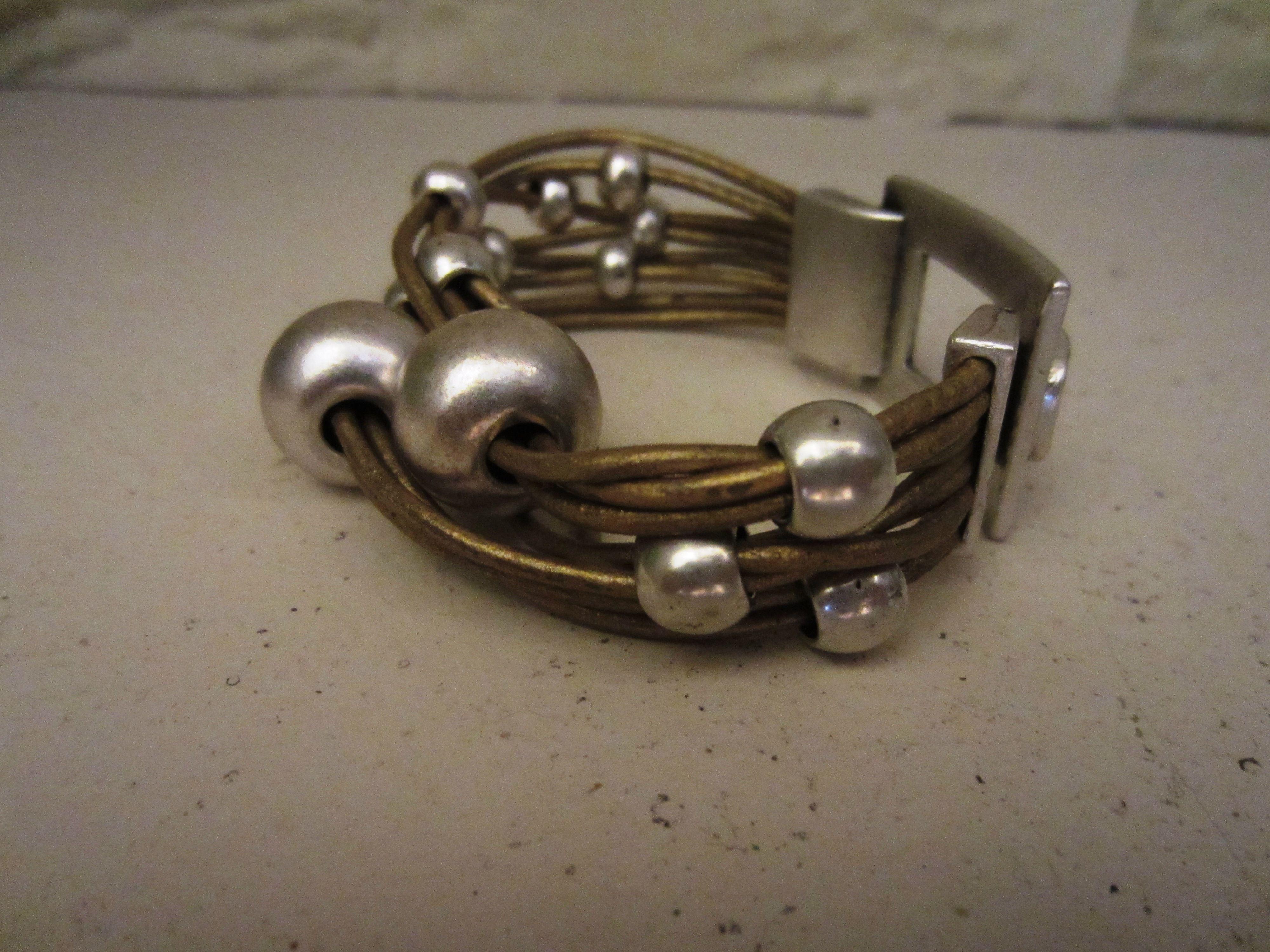 Pulsera realizada en cuero dorado , bolas de diversos tamaños y cierre baño de plata