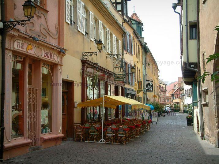 Colmar: Los comerciantes la calle, con sus casas con fachadas de colores y una cafetería - France-Voyage.com
