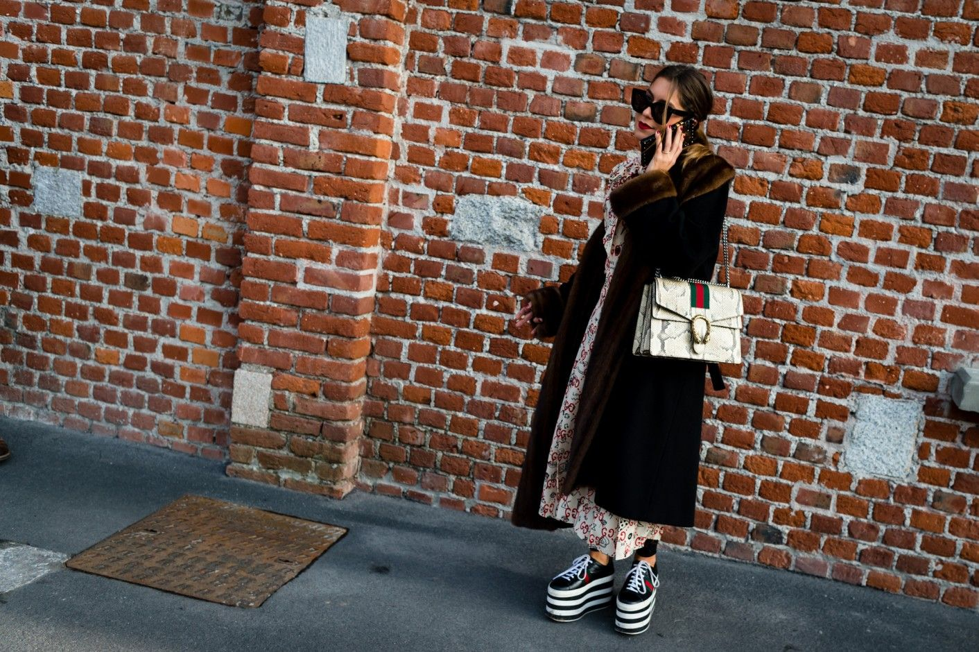 Street Style Photos From Fall 2017 Milan Fashion Week: As such, it follows that Milanese street style would be next-level eccentric and totally inspiring and fantastic. Daniel Kim of Walking Canucks is our man on the ground capturing all the very best of the best of Milan Fashion Week street style. ----- Brown fur jacket, black platform shoes and Gucci purse.     Coveteur.com