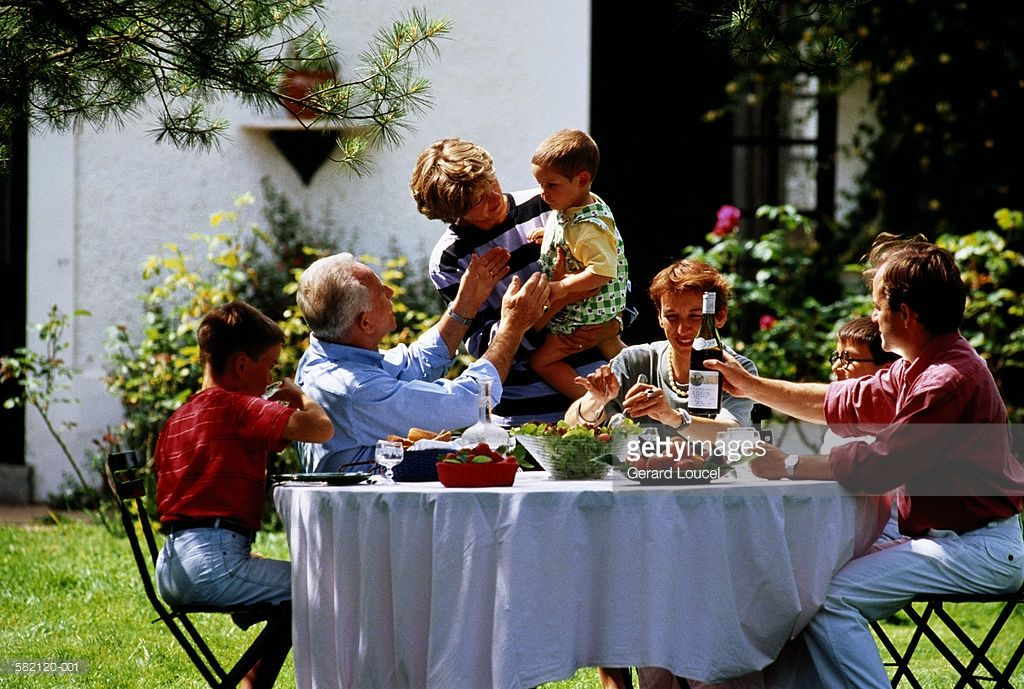 Three generation family eating meal outdoors