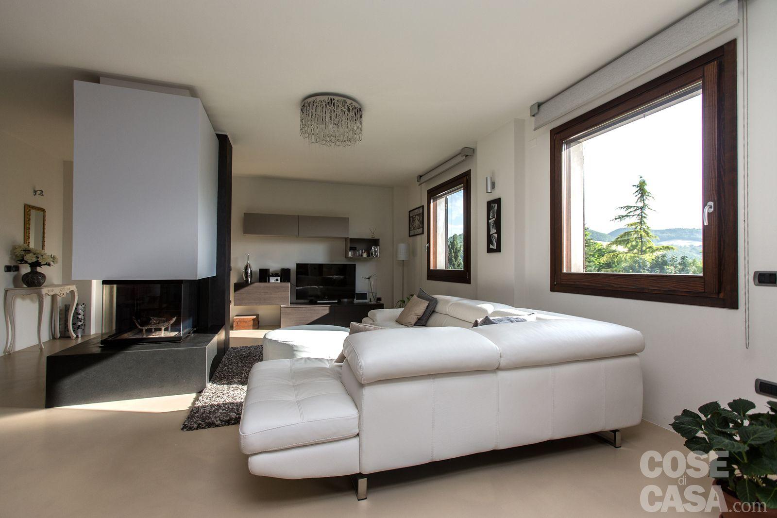 Il grande divano bianco ad angolo a cinque ampie sedute delimita ...