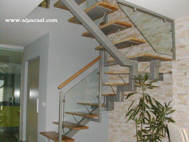 Escalera con eje central metálico, pasos en madera maciza de Roble y