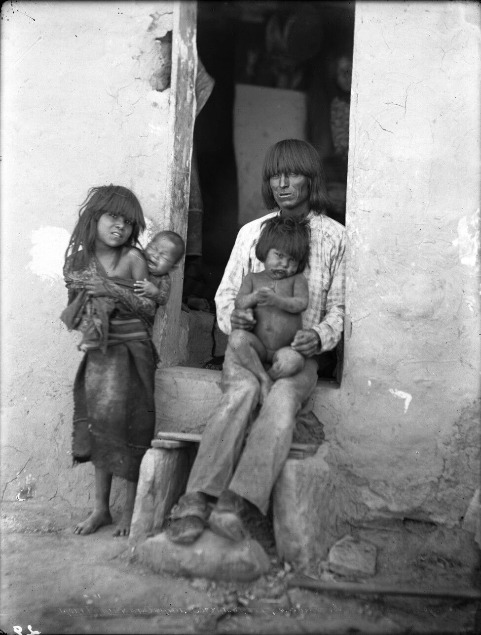 Hopi Indian father sitting in the wood framed doorway of ...
