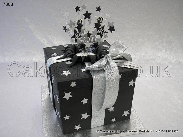 Black and silver themed birthday surprise present parcel box celebration cake in black with silver stars. Finished with silver glitter ribbon, topped with a bursting out matching 40 starburst topper, and edible gift tag