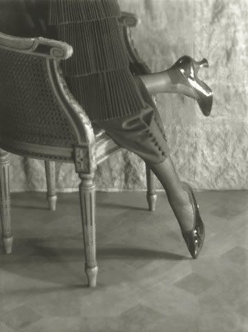 c.1919 Baron de Meyer ,Model Wearing Patent Leather High Heel  View of model's legs, kneeling on a chair in the Empire style, wearing black patent leather shoes with colored tips and heels, by Slater