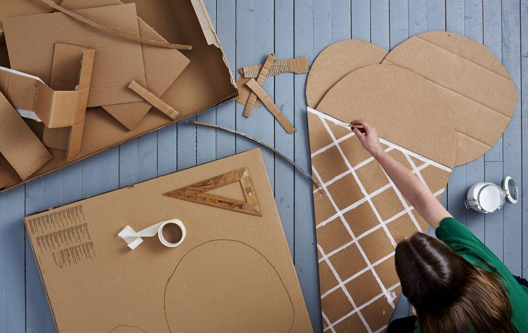 Ein Foto aus der Vogelperspektive. Zu sehen ist eine Frau, die mit einem Stück Karton bastelt und es in Form einer Eiswaffel bemalt.