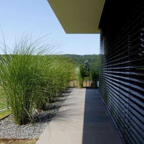 Minimalistische Gartengestaltung am Hang mit Wasserbecken aus Cortenstahl und Feuerstelle #modernegärten