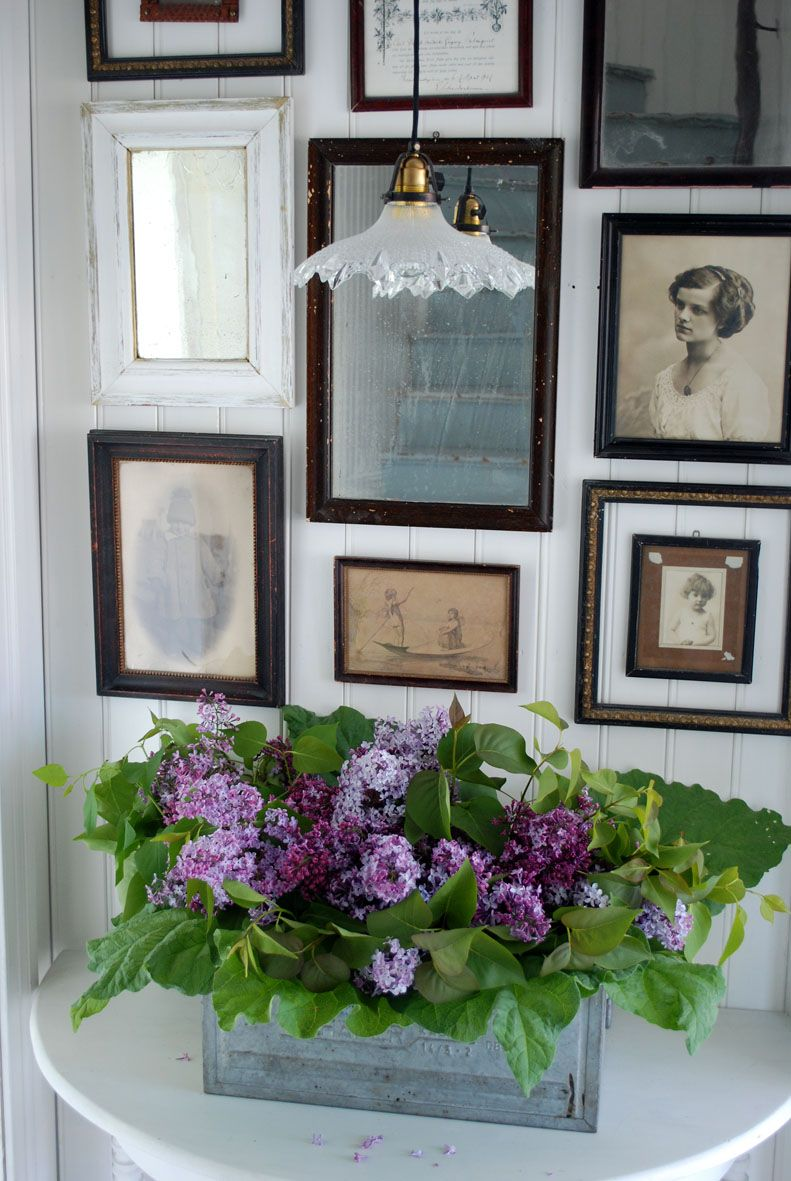 i love this little setting...the table, the old frames, and especially the glass lamp and purple flower arrangement