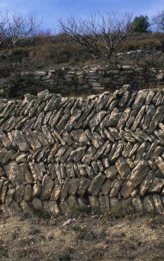 Cabrières-d'Avignon (Vaucluse) : mur de soutènement au parement formé d'une alternance de lits de pierres obliques. © CERAV