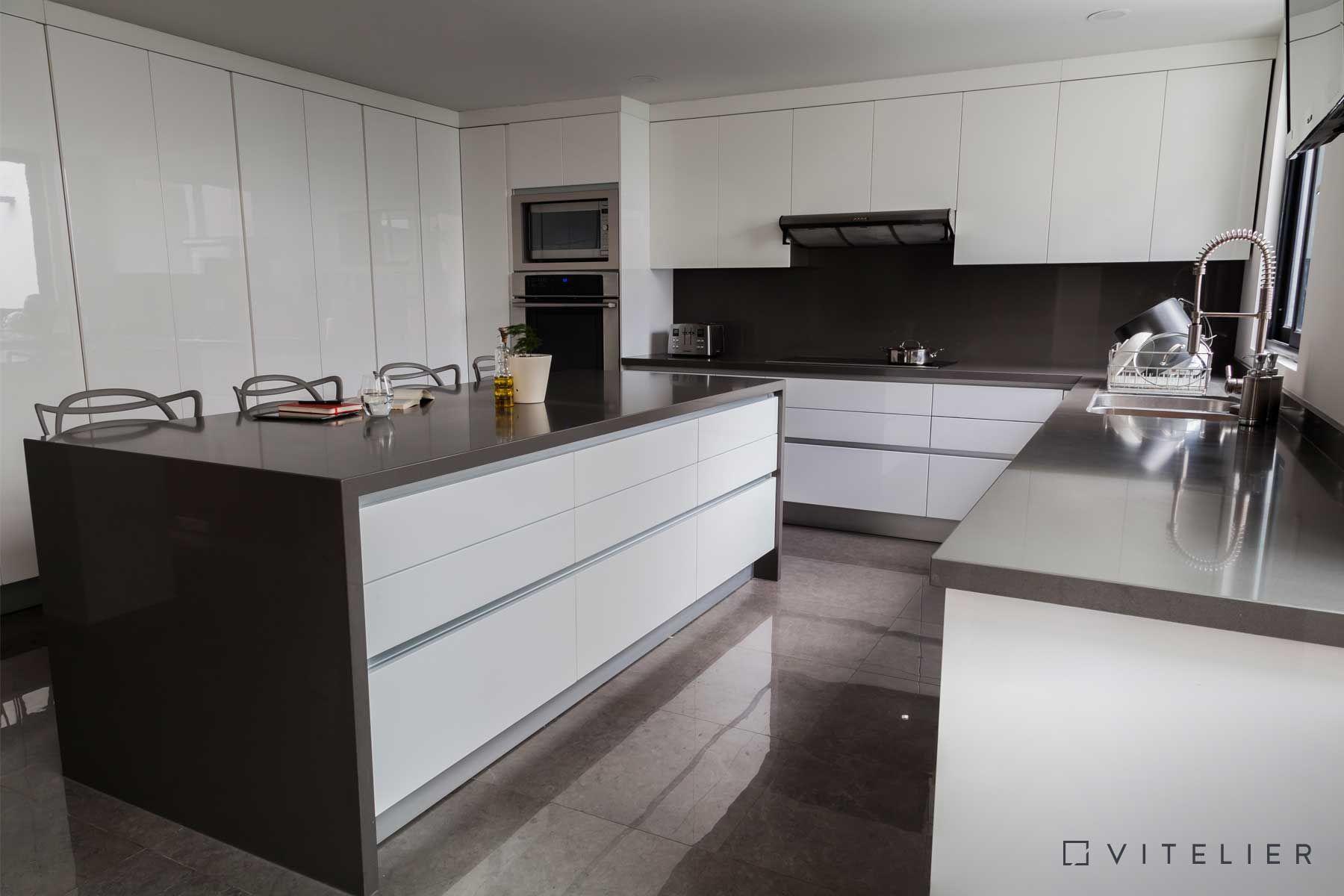 Cocina blanca con cubierta de cuarzo gris para lograr un