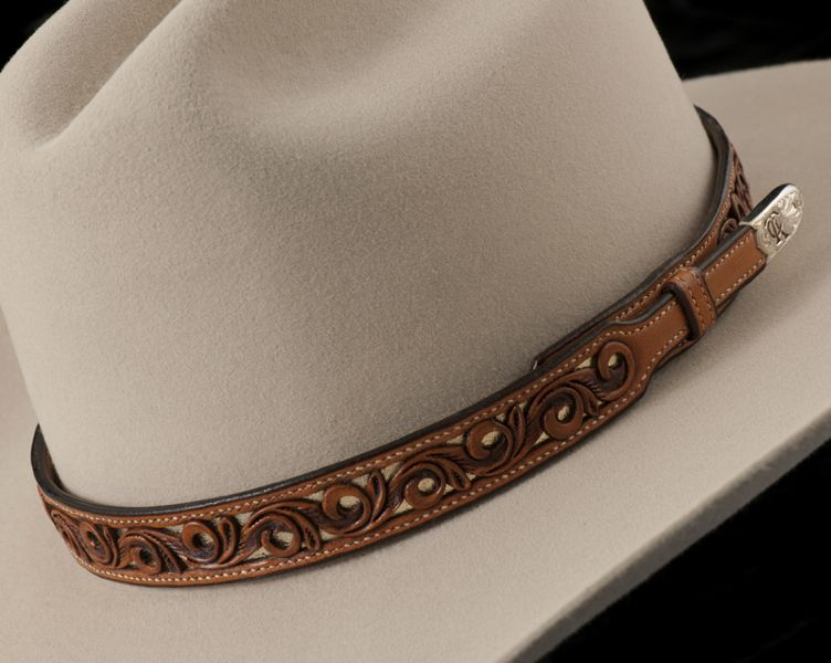 56502fe4548 Pedrini carved a leather hatband that is 7 8 inch wide tapering to 1 2 inch.  It is filigreed throughout with a gold leather background and h.