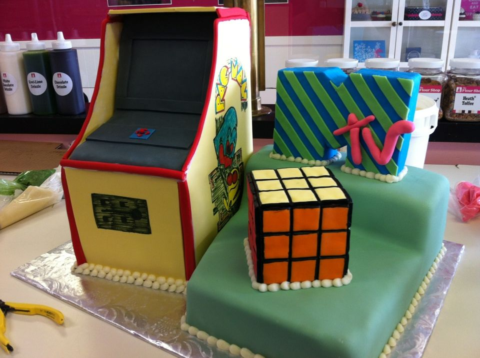 An 80s themed birthday cake complete with a PAC MAN arcade game