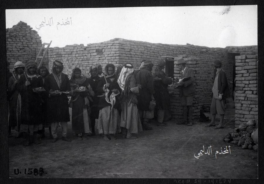صورة من التراث العراقي لعمال يعملون في التنقيب عن الاثار في منطقة اور سنة 1930 ويظهر وهم يقفون لاستلام اجورهم Woolley Inspecting Artifact Photo History Image