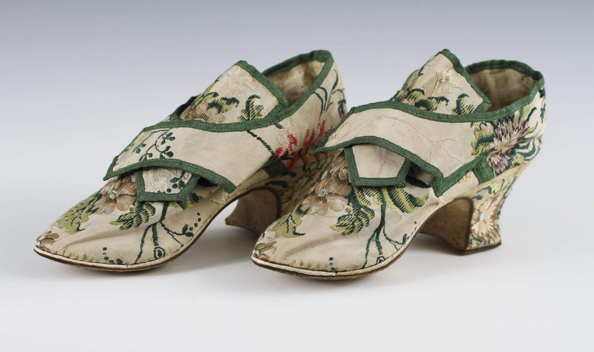Pair of woman's shoes, England (Spitalfileds, probably desined by Anna Maria Garthwaite), c. 1740. Cream silk taffeta brocaded with floral motifs, green silk ribbon, linenn lining.