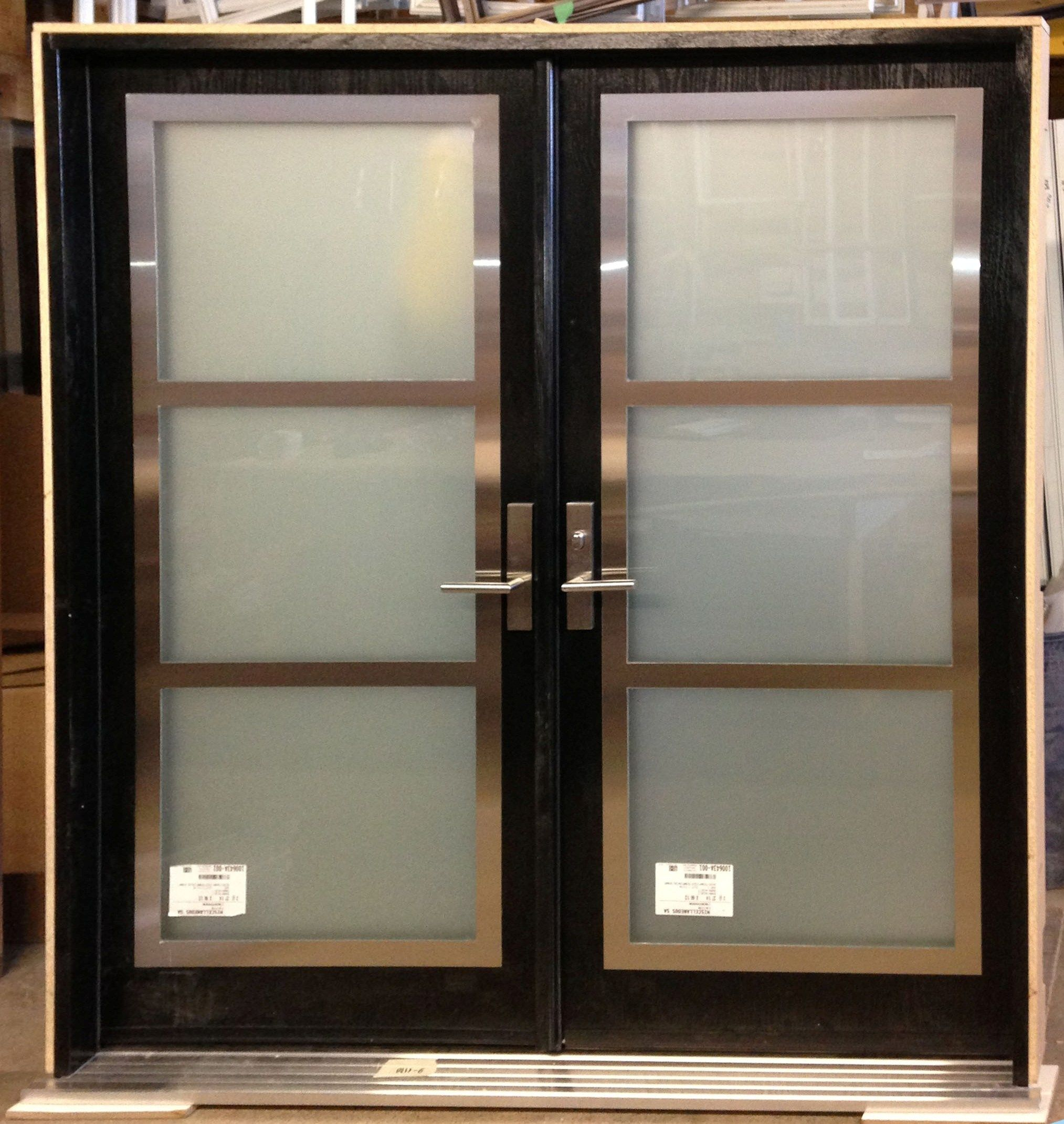 Double entry door with stainless steel frame on top of glass ...