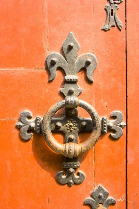 Fleur De Lis Door Knocker On A Orange Door.