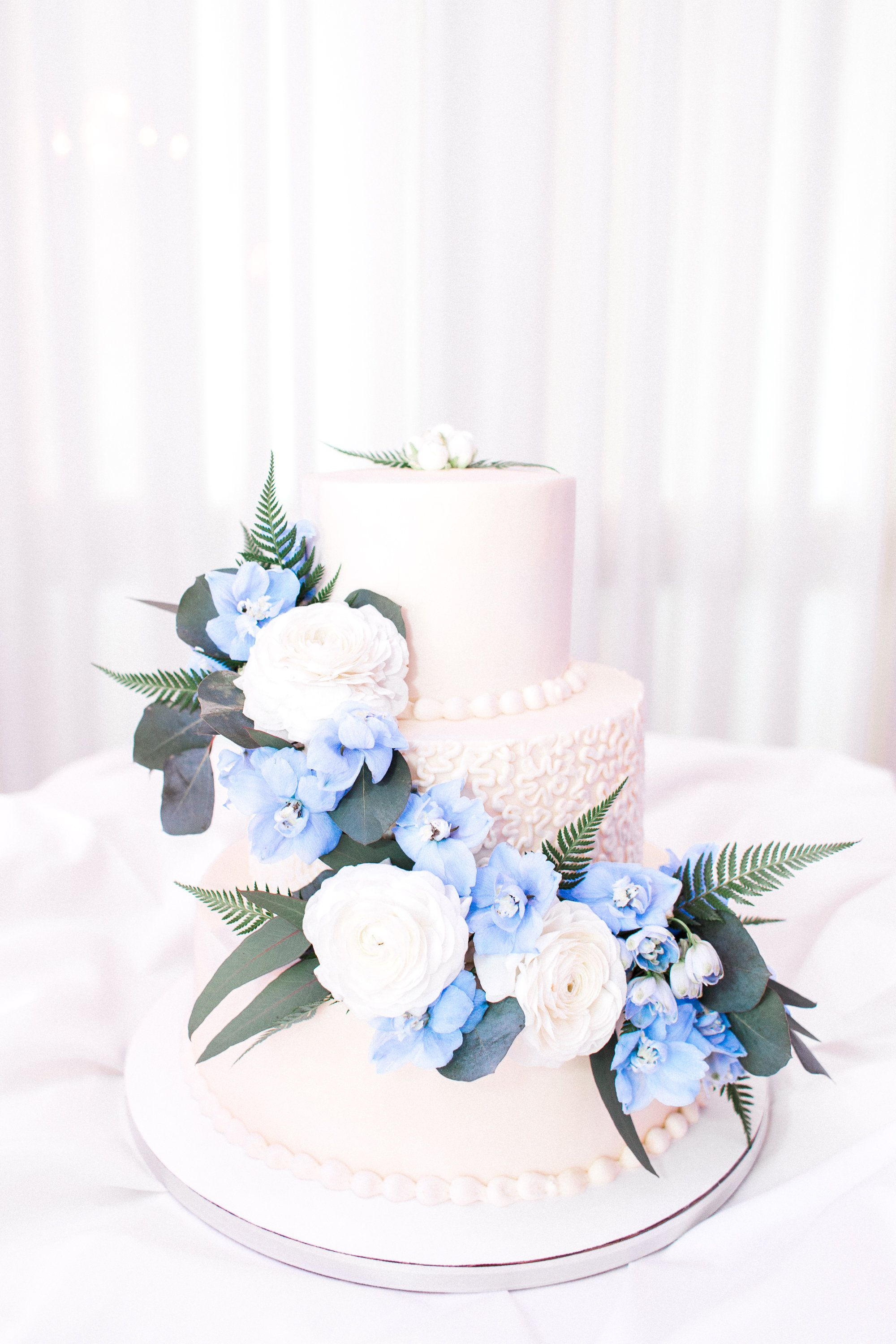 Tiered wedding cake with blue floral accents planning a spring