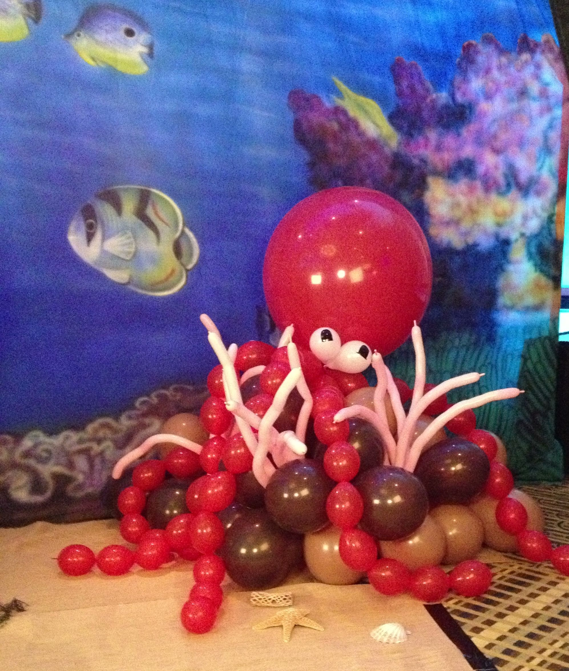 Air Filled Balloon Octopus Placed On Rock Formation With Coral